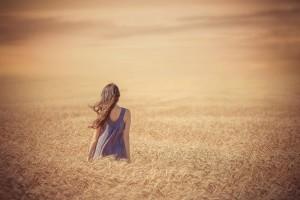 sad-girl-in-purple-dress-walking-through-wheat-field-at-sunset
